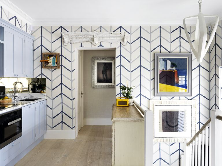 Blue kitchen ideas illustrated by a blue and white chevron wallpaper, pale blue cabinetry and white and yellow accents.