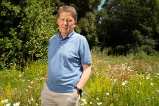Bill Turnbull in a posed shot in a sunny meadow, relaxed with hands in pockets