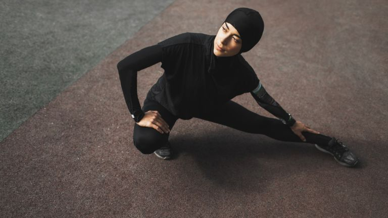 Sweaty Betty to introduce activewear hijab. Young muslim fitness woman in hijab doing stretching exercises outdoors. Dark background with empty place and copy space. Sports concept. Warm up before running training. Black sports clothes. Traditional eastern modest clothing. Healthy lifestyle. Sunny weather.