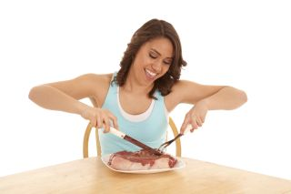 A woman looking super happy to dig into a huge raw steak.