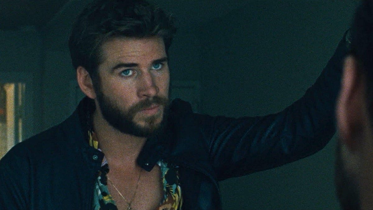 Liam Hemsworth leans against a door in 'Killerman'