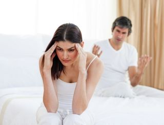 frustrated woman with headache sitting on a bed with partner