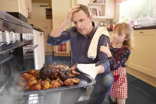 Man takes burnt turkey from the oven.