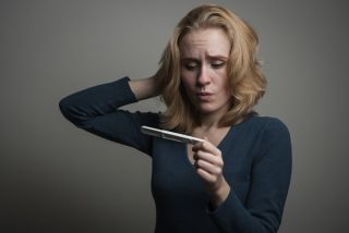 A woman looks confused at a pregnancy test.