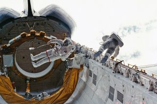 STS-6 crewmates Don Peterson (at right) and Story Musgrave perform the first shuttle-era spacewalk outside Challenger in 1983.