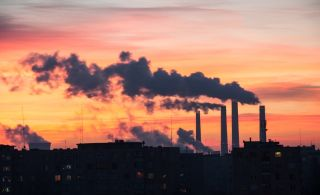 Power Plant emissions seen above residential blocks from a city during sunrise