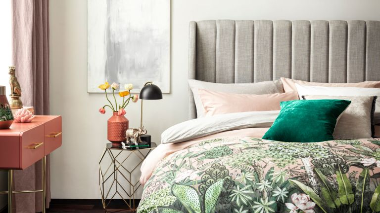 bed with grey headboard and patterned bedsheets