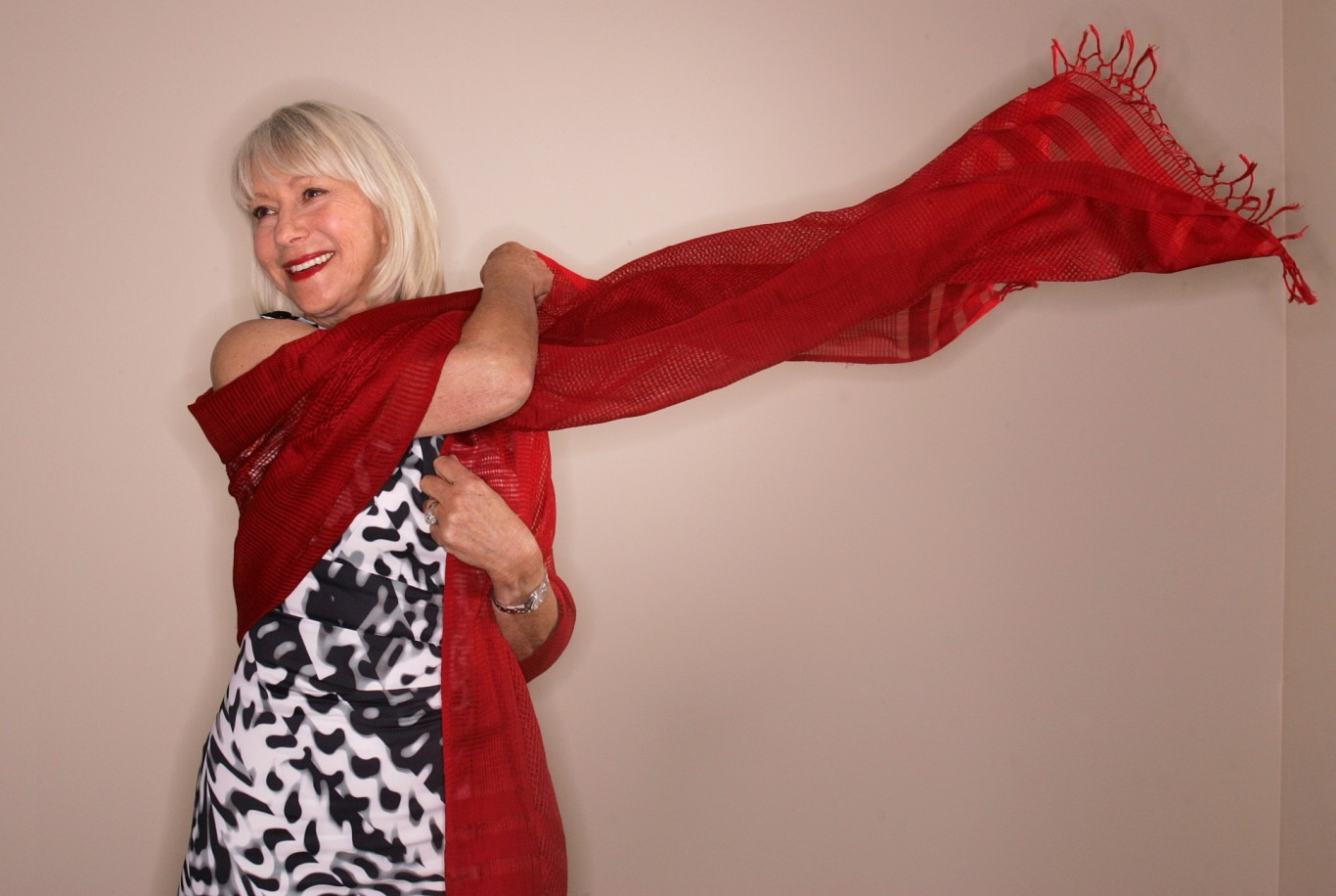 Helen Mirren poses with a red scarf in 2010