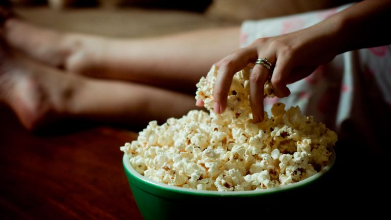 Hand reaches into a bowl of popcorn