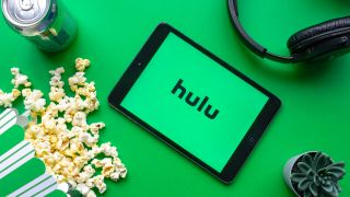 Hulu on a tablet next to food and headphones