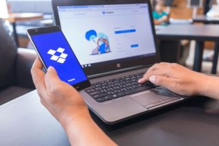 Dropbox open on both a smartphone and a Windows laptop.
