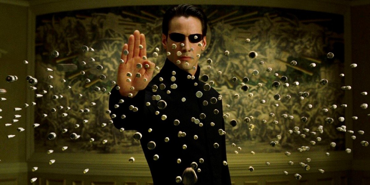 Keanu Reeves as Neo stopping bullets in The Matrix