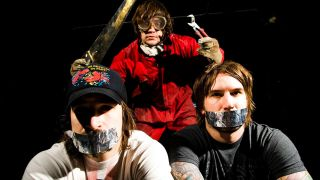 A posed shot of Every Time I Die with tape over their mouths