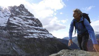Hardshell vs softshell: man hiking next to snowy mountain