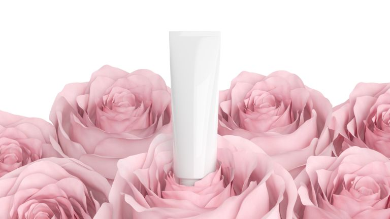 Cosmetic bottle surrounded by pink roses