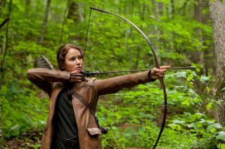 Katniss Everdeen (Jennifer Lawrence) holds a bow and arrow in the movie The Hunger Games.