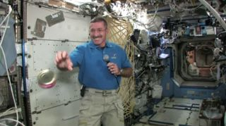 NASA astronaut Dan Burbank catches a floating can of cranberries on the International Space Station just before Thanksgiving.