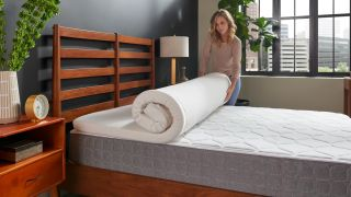 Tempur-Pedic Mattress Topper deal: A woman unrolls the Tempur Topper Supreme on her wooden bed frame