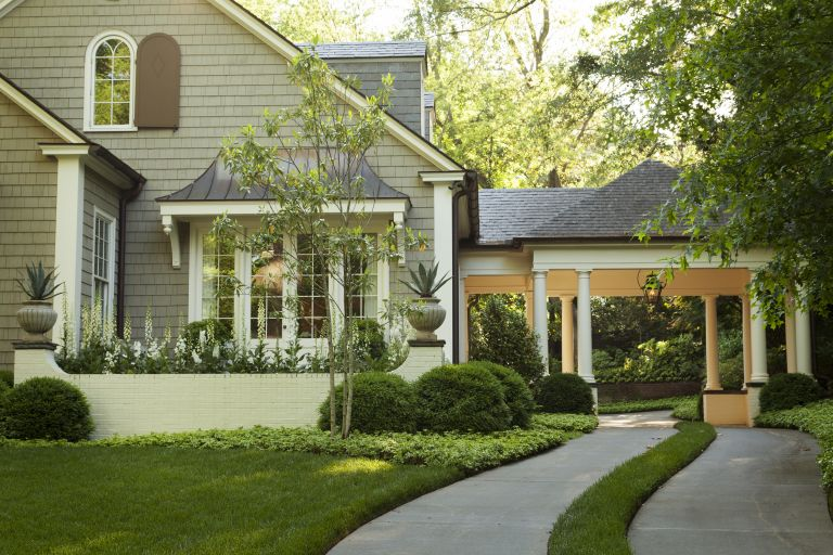 An example of front yard landscaping ideas showing a manicured lawn and concrete driveway way leading up to a covered entrance