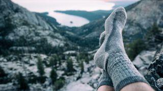 best hiking socks: feet up wearing socks on a mountain range