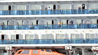 People look out from aboard the Grand Princess cruise ship, operated by Princess Cruises, as it maintains a holding pattern off the coast of San Francisco, California, on March 8, 2020.