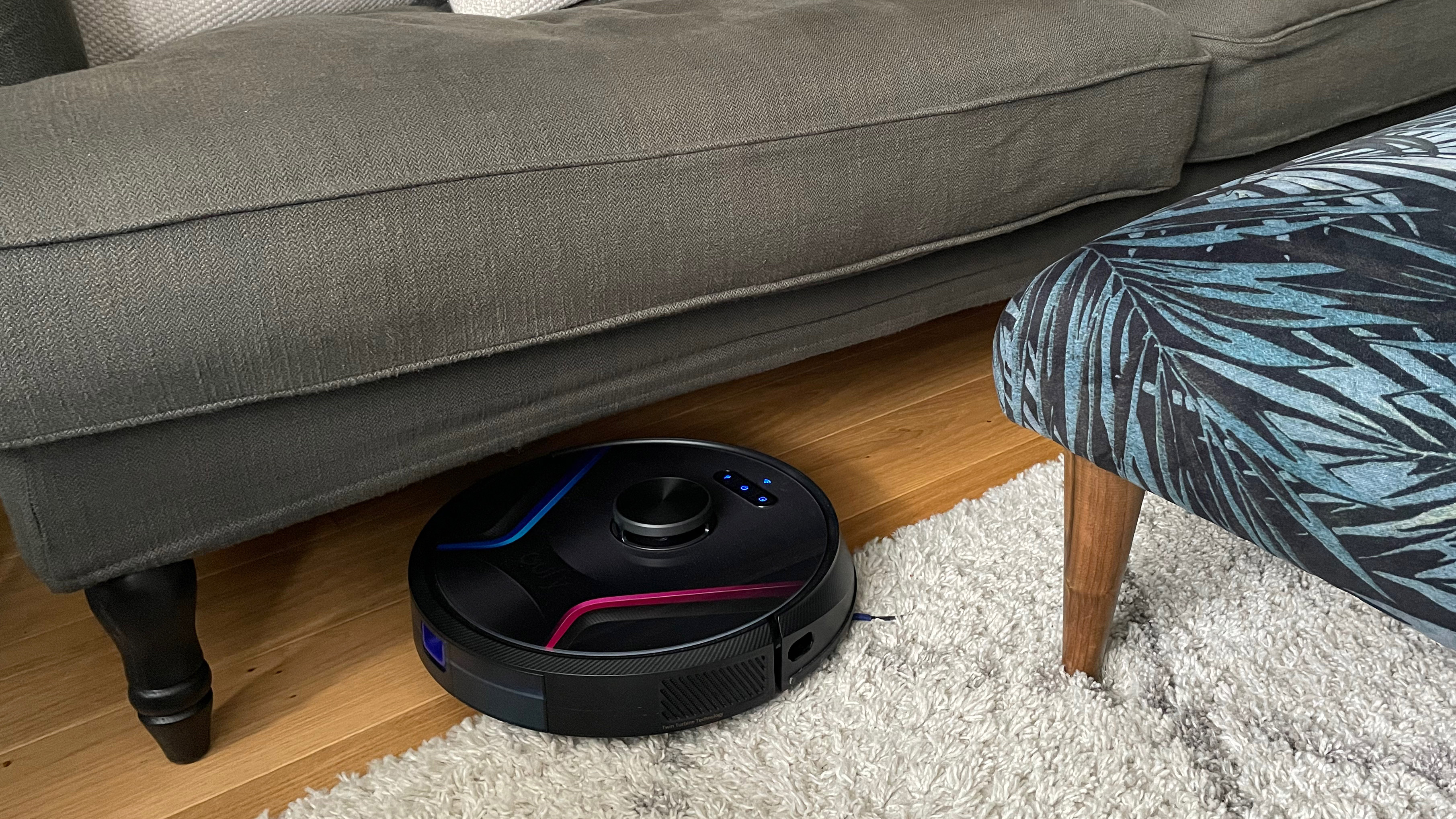 The Eufy RoboVac X8 cleaning a rug on a hard floor surrounded by furniture