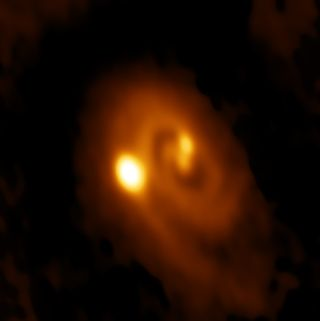 An orange spiral with three bright spots; two near the center and one further out.