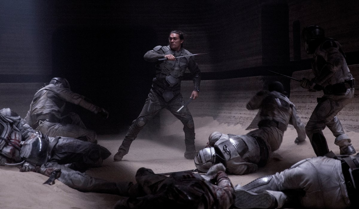 Dune Jason Momoa stands in the middle of his enemies with blades