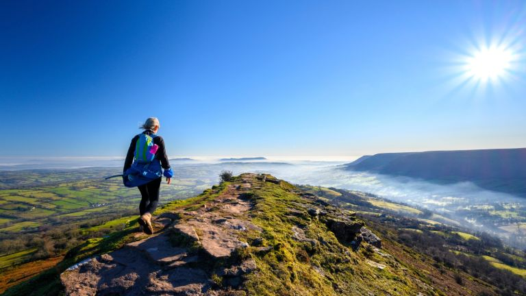 Benefits of walking: woman walking on mountain with views