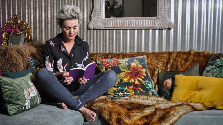 Sarah Parmenter sitting on sofa in her metallic living room