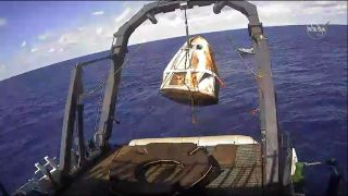 A recovery ship hauls SpaceX's first Crew Dragon capsule out of the Atlantic Ocean after the spacecraft's splashdown on March 8, 2019.