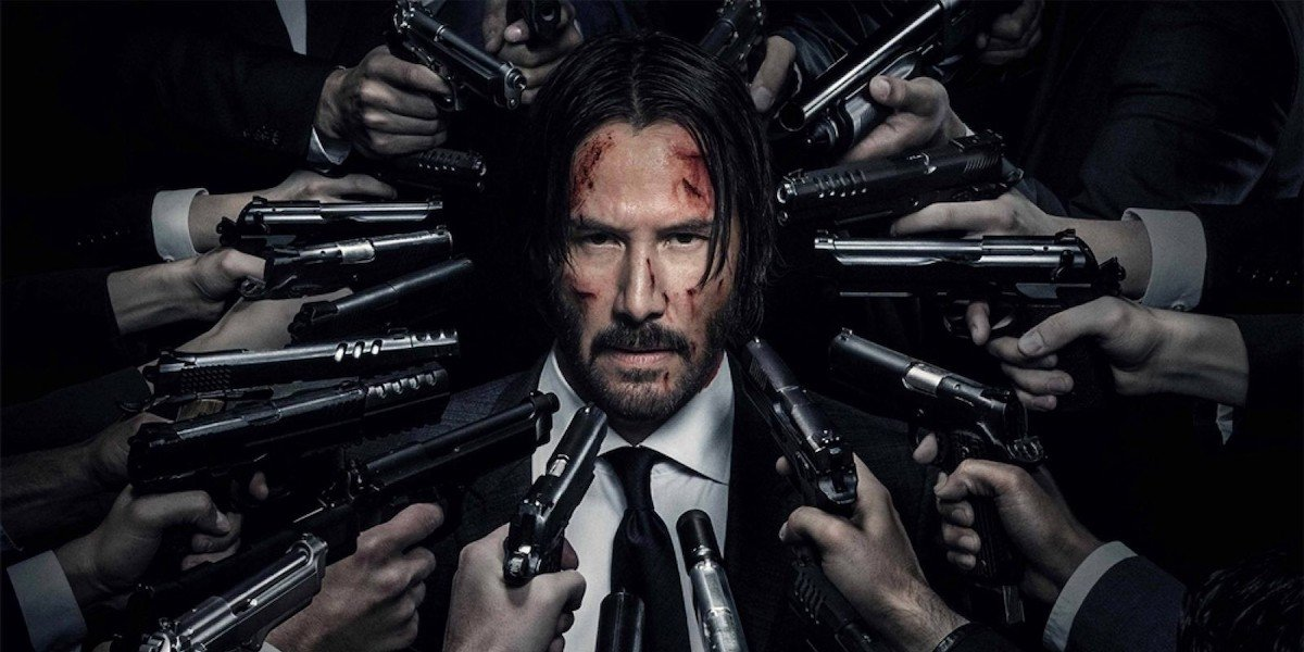 John Wick stands with a whole bunch of guns surrounding his head in a promotional image for the John