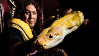 A photograph of Testament's Chuck Billy holding a snake
