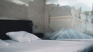 Bedroom with image of outside building projected onto wall