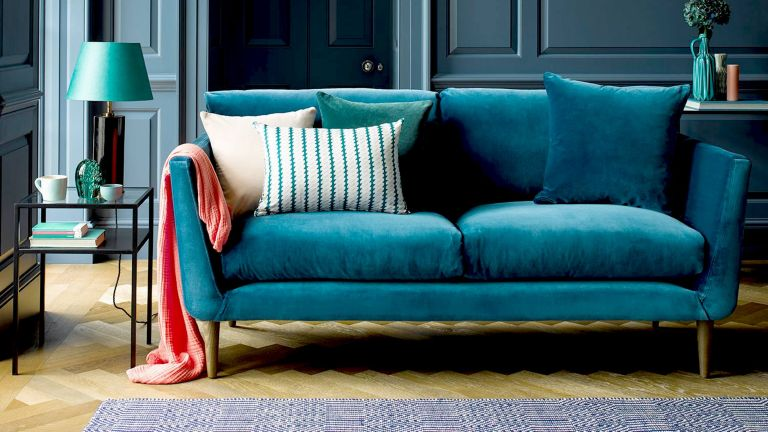 A teal blue velvet sofa with patterned scatter cushions and an orange throw draped over the arm in panelled living room with a metal side table and teal blue lamp