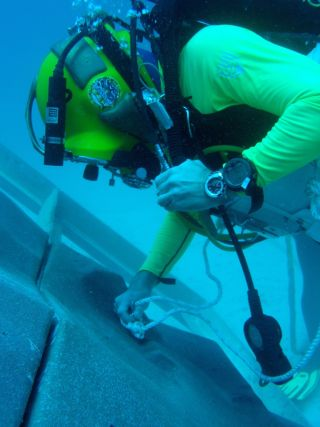 A diver anchoring to a simulated asteroid surface created for NASA's underwater NEEMO 15 mission.