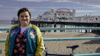 Susan Calman's Grand Week By The Sea: Susan stands on the Brighton seafront, with Brighton Palace Pier in the distance behind her