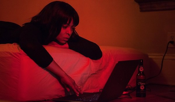 Acrimony Taraji P. Henson browsing on her computer bathed in red light