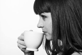 Profile portrait of young woman drinking a cup of coffee, in monochrome.