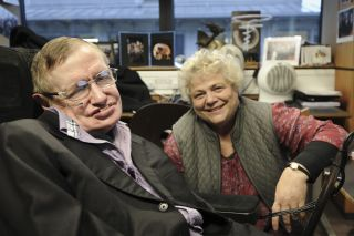 "Stephen Hawking and his assistant Judith Croasdell pose for a portrait in his office at the Department of Applied Mathematics and Theoretical Physics, Cambridge. Hawking is the subject of the PBS documentary ""Hawking"" airing Jan. 29, 2014."