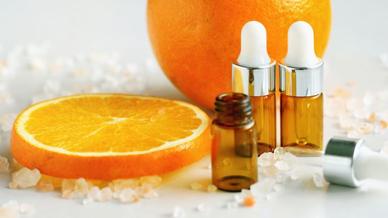 sliced orange with skincare bottles
