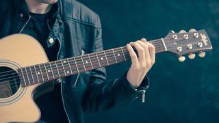 A guitar player fretting a chord
