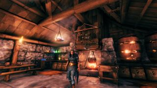 A character stands in front of a Valheim spice rack, which is hanging from a beam above a cauldron