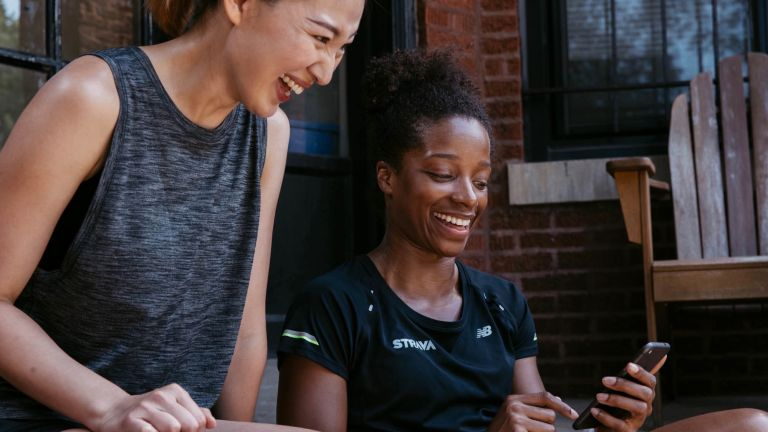 Two fit women working out how to use Strava on their phone