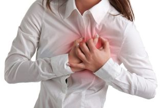 A woman grabs her chest in pain.