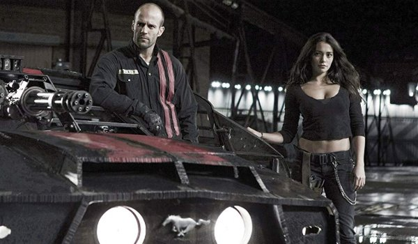 Death Race Jensen and Case stand next to their car in the garage