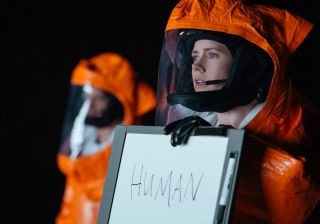 Amy Adams in a hazmat suit holds up a sign which reads 'Human'