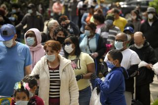 People waiting in line and wearing face masks in Reading, PA on April 25, 2020.