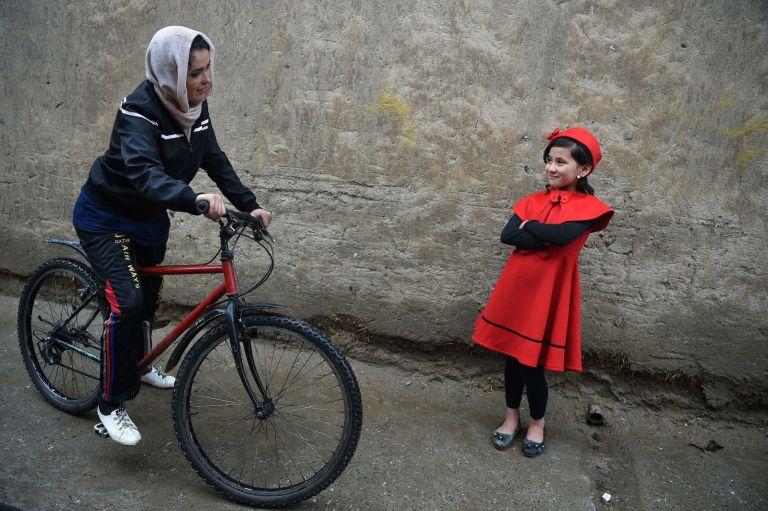 Afghan cyclist Kobra Samim talks with a young girl by a roadside in Kabul