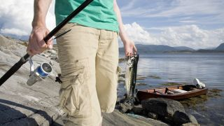 Man holding fishing rod and mackerels